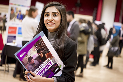 Female at a conference holding a brochure